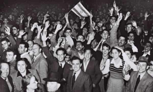 Jubilant Tel Aviv residents celebrate with what would become the Israeli flag after the UN decision to approve the partition of Palestine, 29 November 1947.