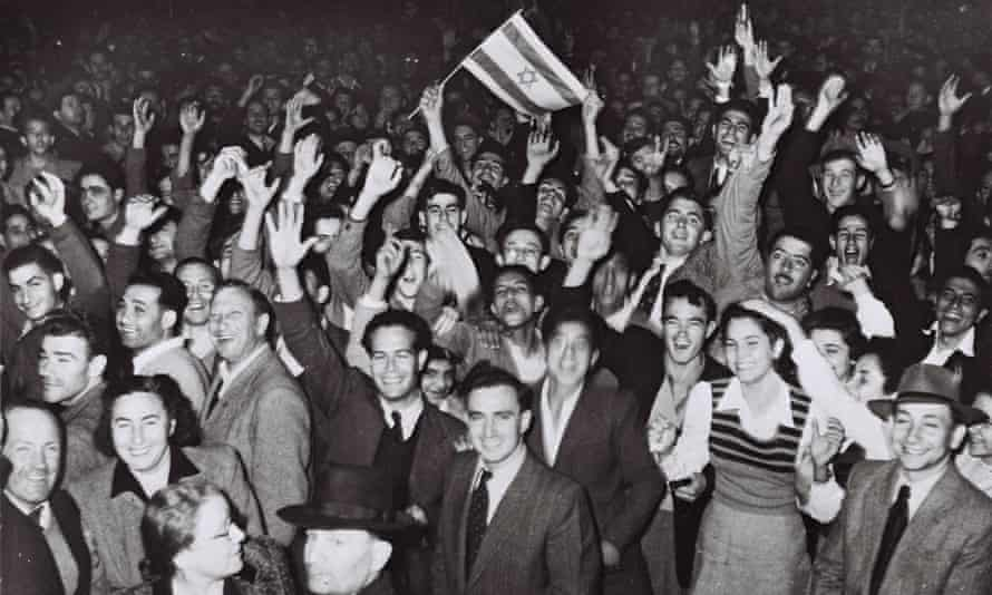 """(FILE) Israel At 60: The Birth Of A NationTEL AVIV, PALESTINE - NOVEMBER 29, 1947: Jubilant residents celebrate with what would become the Israeli flag after the United Nations decision to approve the partition of Palestine November 29, 1947 as crowds gather in front of the Mugrabi cinema in Tel Aviv in the British Mandate for Palestine. (Photo by Hans Pins/GPO via Getty Images) """""""