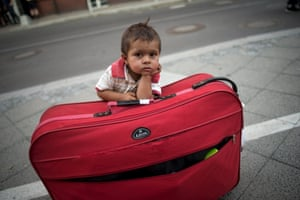 A migrant boy waits at his parents' suitcase as they  apply for asylum in Berlin
