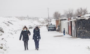 A nurse and a doctor walk through La Cañada Real after visiting a child suffering hypothermia in one of the houses