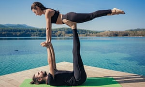 Couple practicing acroyoga in nature at beautiful lake Acroyoga front plank pose