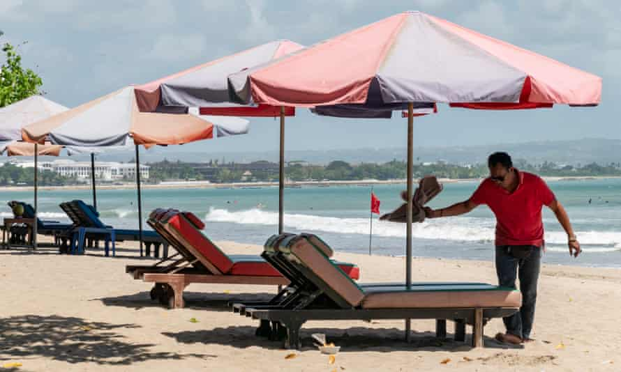 A man sets up sea-side loungers at a beach in Kuta, Bali, Indonesia