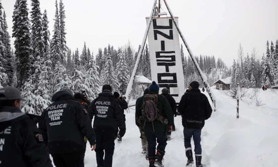 RCMP officers join hereditary chiefs and supporters as they walk towards the Unist'ot'en anti-pipeline camp on 9 January 2019.