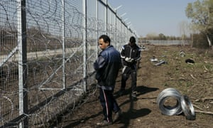 Workers attach barbed wire to a fence at the Bulgarian-Turkish border near the Bulgarian village of Shtit.