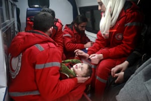 Staff from the International Committee of the Red Cross assist a child during an evacuation in Douma, Syria