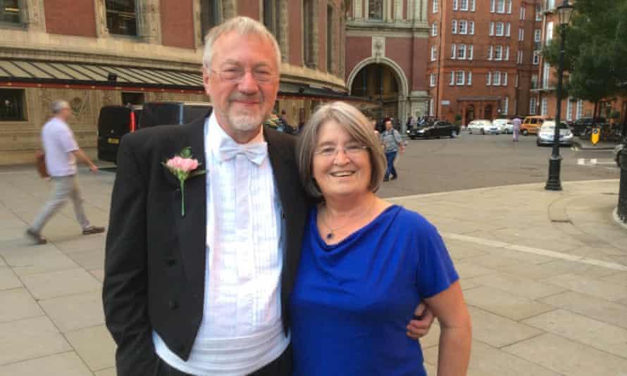 Christopher Larkin and Patricia Larkin with their arms round each other, he wearing full white-tie and a buttonhole, she wearing a blue dress, with the Albert Hall int he background