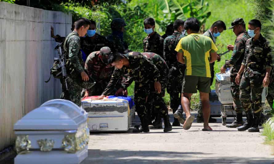 Philippine troops place a flag on a case containing the body of a comrade killed during an assault against insurgents in Marawi.