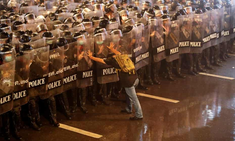 A protester with riot police during a protest calling for reform of the monarchy in Bangkok, Thailand, 16 October 2020
