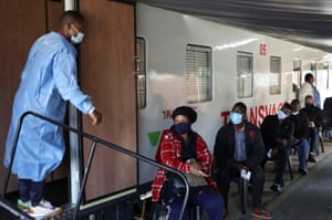 A health worker talks to people as they wait to register next to the Transvaco coronavirus disease (COVID-19) vaccine train at the Springs train station on the East Rand, South Africa.