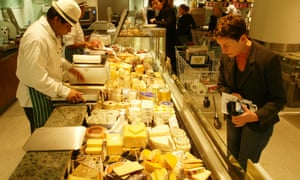 Shoppers at cheese counter.