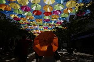 A woman walks with an umbrella through an art installation called Umbrella Sky in Coral Gables in Florida