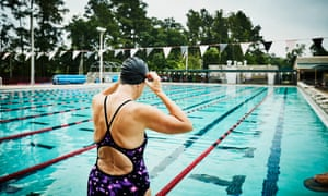 Mature woman adjusting goggles at side of outdoor pool before morning workout