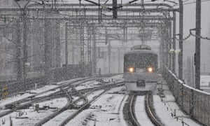 A train approaches a station as snow falls in Tokyo.