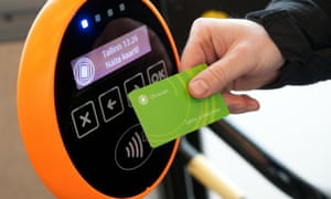 A passenger holds his ticket card to a scanner aboard a public transport bus in Tallinn,
