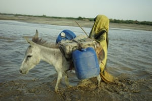 A woman walks a donkey with two water cannisters strapped to its back.