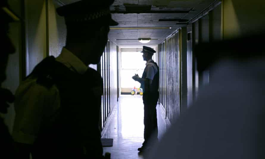 two male police officers in a dark corridor