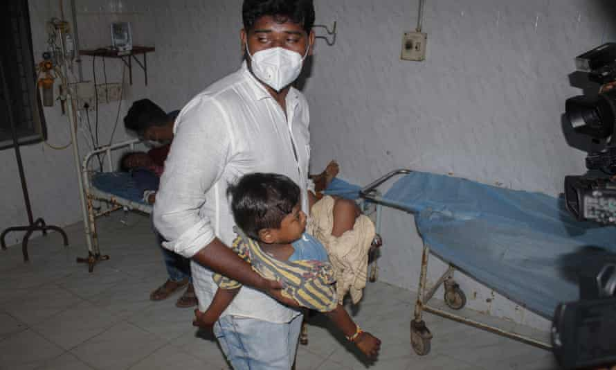 A young patient is carried by a man at the district government hospital in Eluru, Andhra Pradesh state, India)