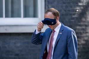 London, UK. Health Secretary Matt Hancock removes his face mask as he arrives on Downing Street