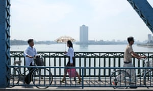 Pedestrians walk on the newly painted Taedong Bridge in Pyongyang