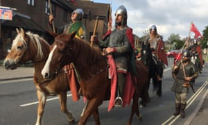 Bunch of men in 11th-century armour on horses, in a modern street