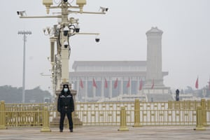 A Chinese police officer guards an empty Tiananmen Square near the Great Hall of the People in Beijing. China has reverted back to holding its annual Congress meetings in March after delaying them due to the outbreak of coronavirus last year. Security was tightened in the capital with troops patrolling near the Great Hall where the meetings are held and standing guard at subway stations.