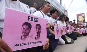 Protesters kneel silently with images of the Reuters journalists in Myanmar.