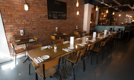 A long wooden table with metal-framed wooden chairs and, on the brick wall, a chalkboard with writing on it