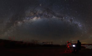 The Milky Way curves across the sky, watched by a lone astronomer.
