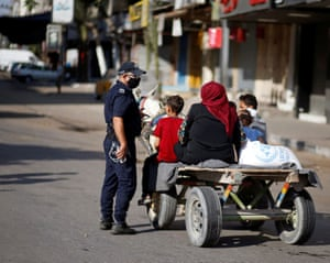 A police officer speaks with Palestinians riding a donkey-drawn cart during lockdown after Gaza reported its first cases of Covid-19 in the general population.