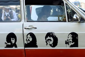 An image of The Beatles is displayed on the side of a car in the city's downtown area, La Paz