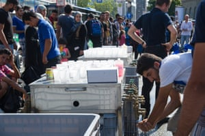 Refugees drink from water taps outside Munich central station