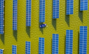 Haian, China: Workers check solar panels at a photovoltaic power station built in a fishpond in Jiangsu province