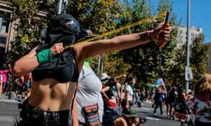 A protestor in Santiago, Chile aims a slingshot at riot police.