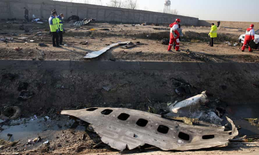 Emergency services personnel walk amidst the wreckage after an Ukraine International Airlines Boeing 737-800 crashed.