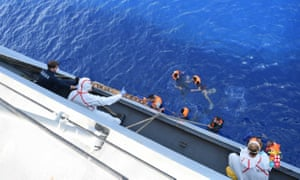 People are helped to board an Italian navy ship after a boat overturned off the Libyan coast