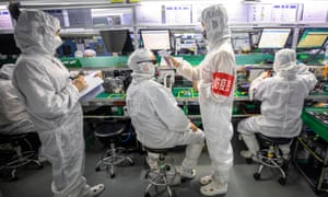 Security employees on duty check their colleagues' temperature at their workstations in Appotronics factory in Shenzhen, amid coronavirus outbreak in China.