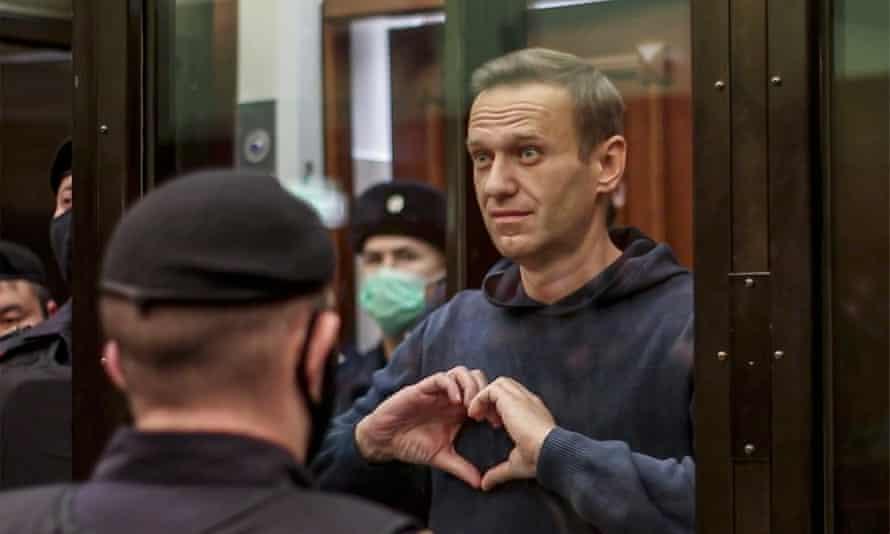 Навальный от души жестикулирует руками в окружении сотрудников в форме.