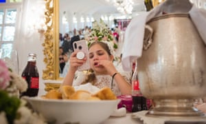 Maria on her phone during her first communion lunch that will last almost the whole day.
