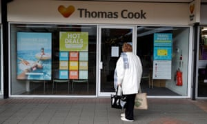 Woman looking into a closed Thomas Cook store