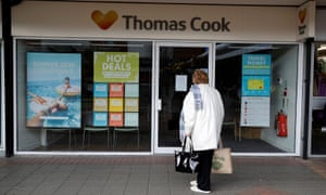 A woman stands outside a closed Thomas Cook travel agents store near Manchester.