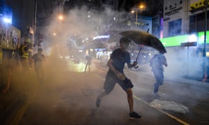 Protesters react after police fired tear gas in the Mong Kok district of Hong Kong.