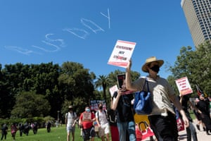 Protesters march through Hyde Park with the words Aus Day in the sky above them.