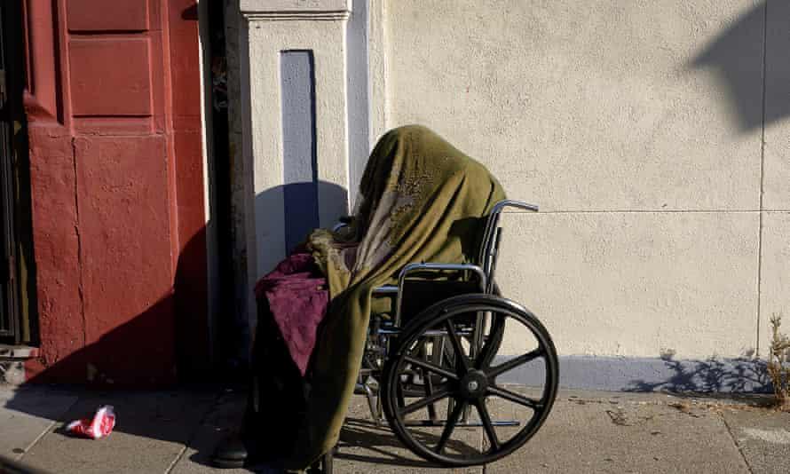 A person sits in a wheelchair on a sidewalk in the Tenderloin.