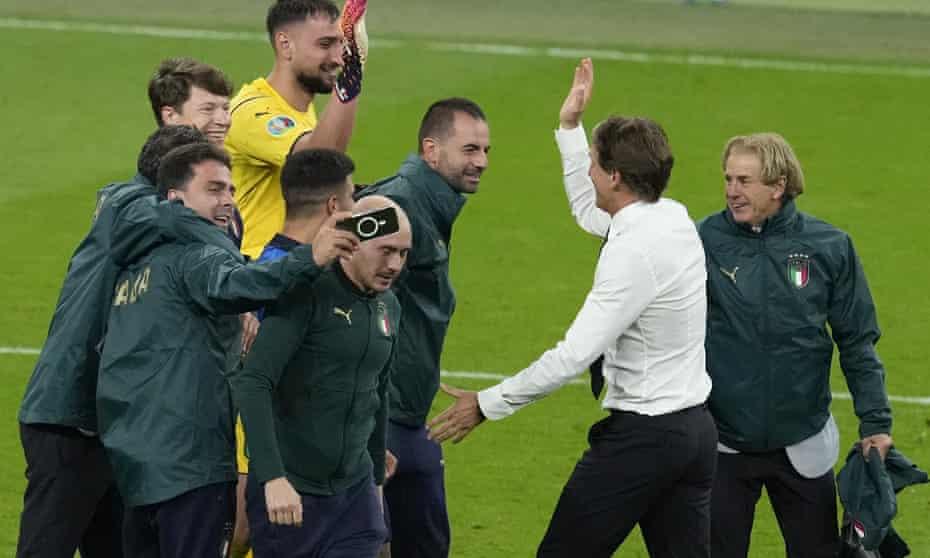 Italian coach Roberto Mancini (second from right) congratulates his goalkeeper Gianluigi Donnarumma after beating Spain on penalties.