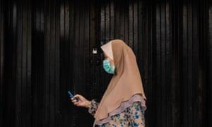 A woman walks past a closed shop in Kuala Lumpur, Malaysia, during the nationwide coronavirus lockdown.