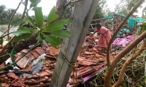 A woman clears debris from her home damaged by Cyclone Bulbul in Bakkhali, West Bengal.