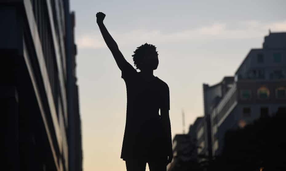 A demonstrator's silhouette is seen as they raise a fist during a protest against police brutality near the White House in Washington, DC.