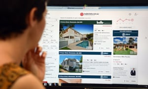 A woman looks at real estate advertising on an internet website in Brisbane