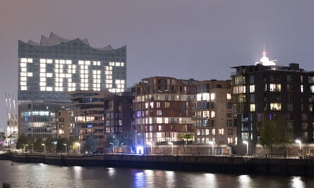 The word 'finished' illuminates the facade of the just-completed Elbphilharmonie concert hall in Hamburg
