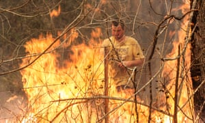 Ian Wheeler fights a fire on his neighbour's property in Killabakh, NSW, 13 November 2019.